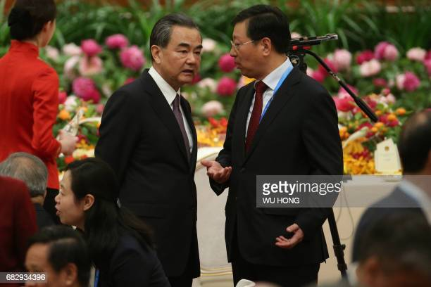 Chinese Foreign Minister Wang Yi listens to a member of a staff ahead of a welcome banquet for the Belt and Road Forum at the Great Hall of the...
