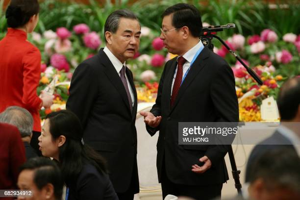 Chinese Foreign Minister Wang Yi listens to a staff during a welcome ceremony for leaders attending the Belt and Road Forum in Beijing's Great Hall...