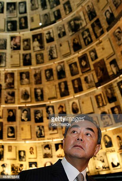 Chinese Foreign Minister Wang Yi looks at pictures of Jewish Holocaust victims at the Hall of Names on December 19 2013 during his visit to the Yad...