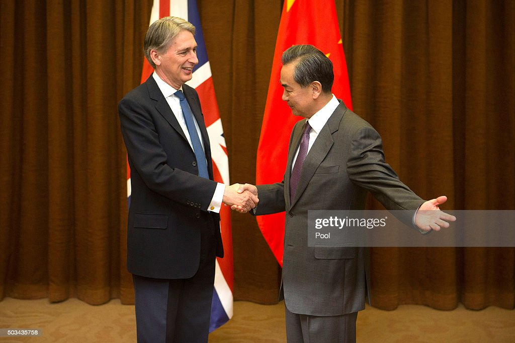 Chinese Foreign Minister Wang Yi, right, gestures to British Foreign Secretary Philip Hammond, left, as he arrives for a meeting at the Ministry of Foreign Affairson January 5, 2016 in Beijing, China.