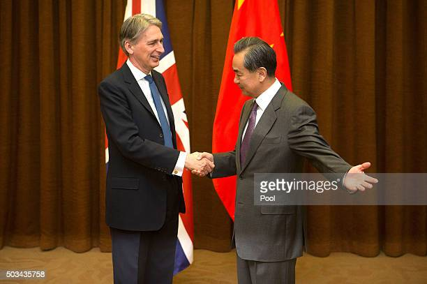 Chinese Foreign Minister Wang Yi right gestures to British Foreign Secretary Philip Hammond left as he arrives for a meeting at the Ministry of...