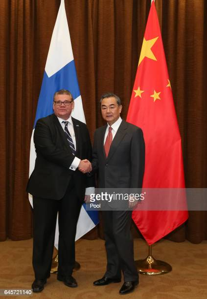 Chinese Foreign Minister Wang Yi shakes hands with Finnish Foreign Minister Timo Soini during their meeting at the Ministry of Foreign Affairs on...
