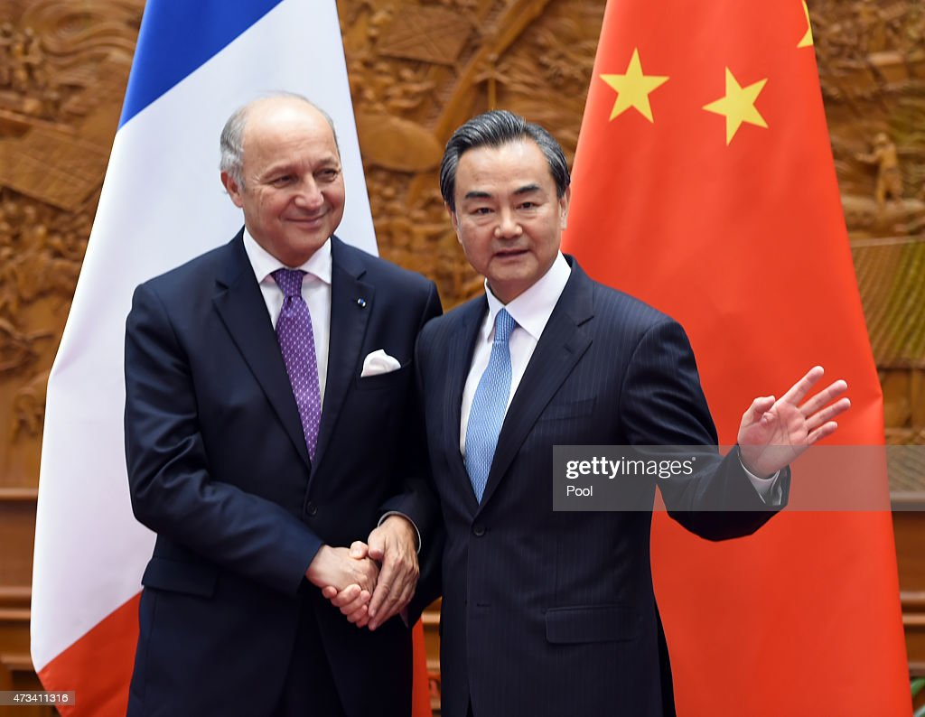 Chinese Foreign Minister Wang Yi (R) shakes hands with his French counterpart Laurent Fabius prior to a meeting on May 15, 2015 in Beijing, China. Fabius is on a two-day visit to China.