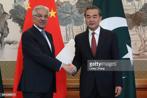 Chinese Foreign Minister Wang Yi shakes hands with Pakistan Foreign Minister Khawaja Muhammad Asif during a press conference at Diaoyutai State...