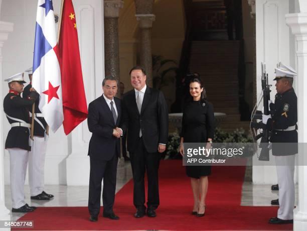 Chinese Foreign Minister Wang Yi shakes hands with Panamanian President Juan Carlos Varela next to Panamanian Foreign Minister Isabel De Saint Malo...