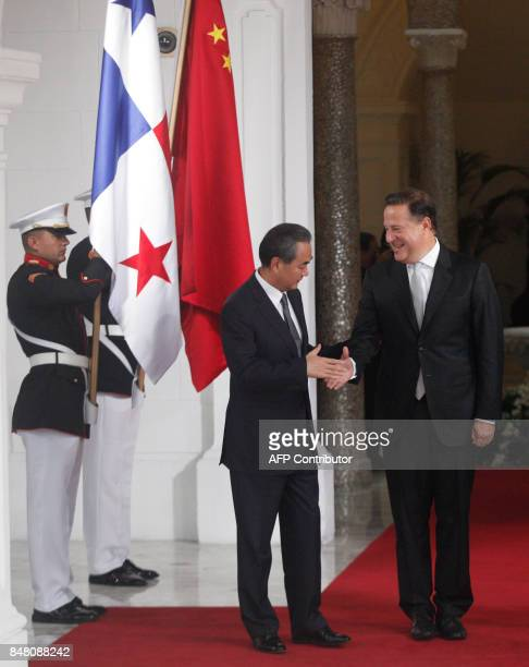 Chinese Foreign Minister Wang Yi shakes hands with Panamanian President Juan Carlos Varela in the presidential palace in Panama City on September 16...
