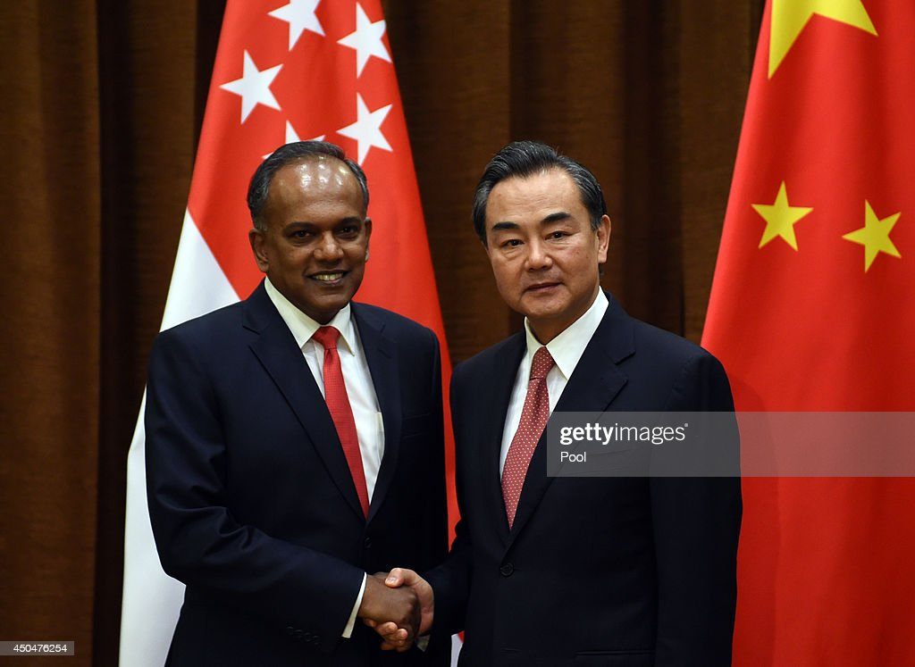 Chinese Foreign Minister Wang Yi (R) shakes hands with Singapore's Foreign Minister K. Shanmugam on June 12, 2014 in Beijing, China.