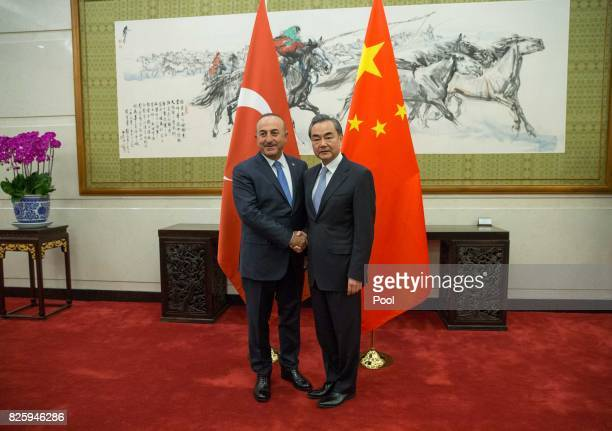 Chinese Foreign Minister Wang Yi shakes hands with Turkish Foreign Minister Mevlut Cavusoglu during their meeting at Diaoyutai State Guesthouse...