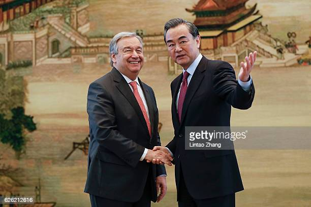 Chinese Foreign Minister Wang Yi shakes hands with United Nations Secretary Generaldesignate Antonio Guterres after a joint press conference at the...