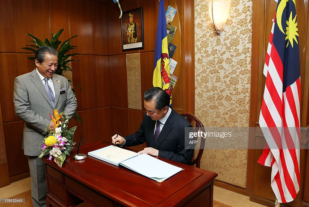 Chinese Foreign Minister Wang Yi (R) signs a guest book as his Malaysian counterpart Anifah Aman (L) looks on prior to a meeting at the foreign ministry in Putrajaya on August 1, 2013. Wang Yi arrived on an official visit to hold talks with Malaysian officials on bilateral and regional issues. AFP PHOTO / POOL / VINCENT THIAN
