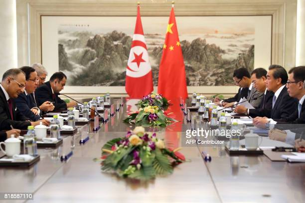 Chinese Foreign Minister Wang Yi speaks as Tunisia's Foreign Minister Khemaies Jhinaoui listens during a meeting at the Ministry of Foreign Affairs...