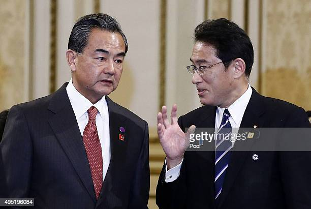 Chinese Foreign Minister Wang Yi talks with Japanese foreign minister Fumio Kishida before the sixth trilateral summit meeting at the presidential...