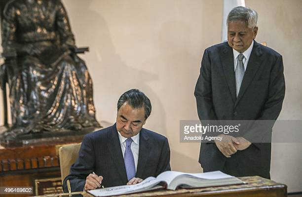 Chinese Foreign Minster Wang Yi signs a guest book prior to a meeting with Philippine Foreign Secretary Albert Del Rosario at the Department of...