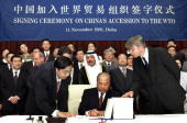 Chinese Foreign Trade and Economic Cooperation Minister Shi Guangsheng signs his country's Wolrd Trade Organization accession documents during a...