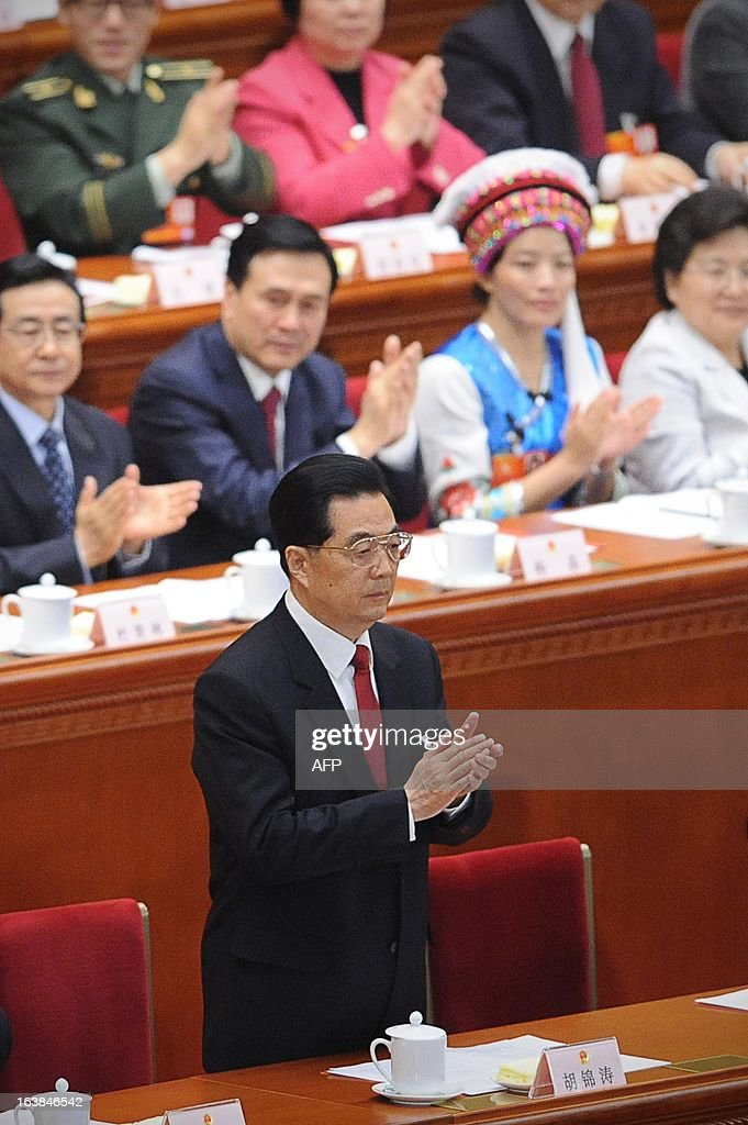 Chinese former president Hu Jintao applauds as President Xi Jinping (not pictured) delivers his maiden speech at the closing session of the National People's Congress (NPC) at the Great Hall of the People in Beijing on March 17, 2013. Xi said he would fight for a 'great renaissance of the Chinese nation', in his first speech as head of state of the world's most populous country. AFP PHOTO /WANG ZHAO