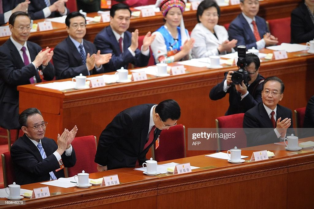 Chinese former president Hu Jintao (C) bows to delegates as President Xi Jinping (not pictured) delivers his maiden speech at the closing session of the National People's Congress (NPC) at the Great Hall of the People in Beijing on March 17, 2013. Xi said he would fight for a 'great renaissance of the Chinese nation', in his first speech as head of state of the world's most populous country. AFP PHOTO /WANG ZHAO