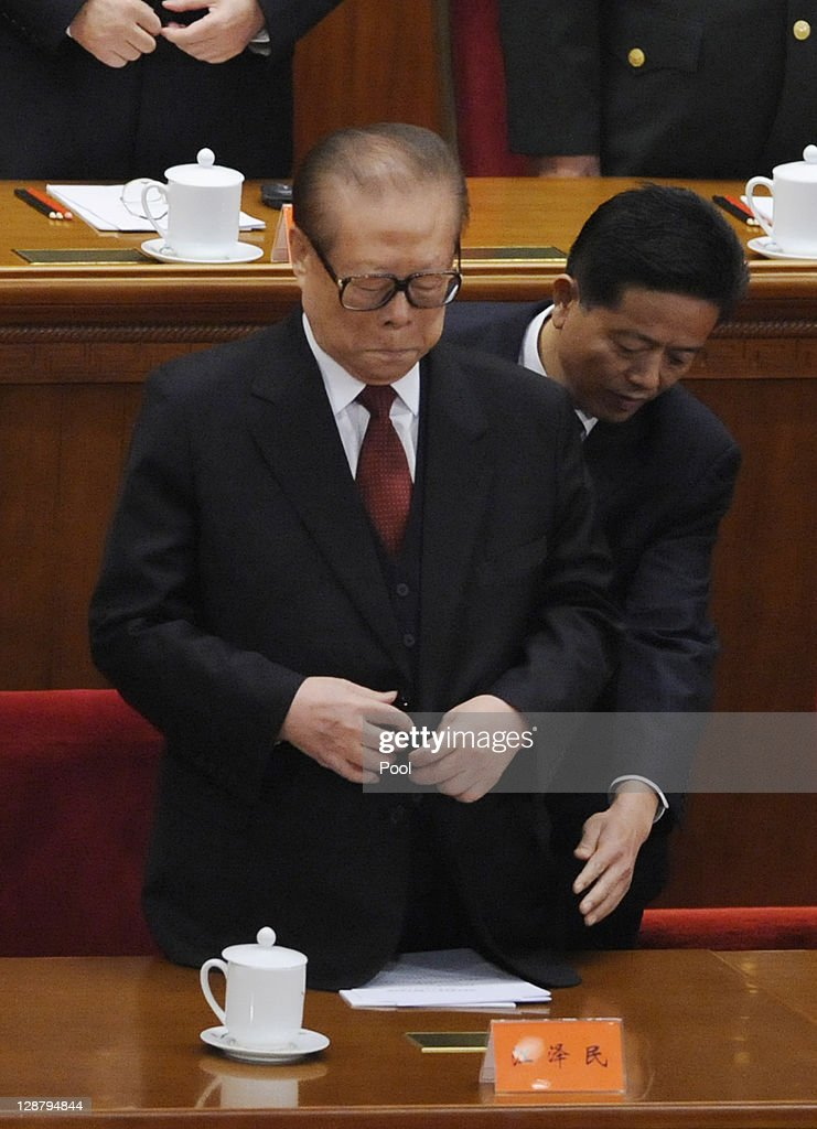 Chinese former president Jiang Zemin is assisted by a staff member at the Commemoration of the 100th anniversary of the Xinhai Revolution at the...