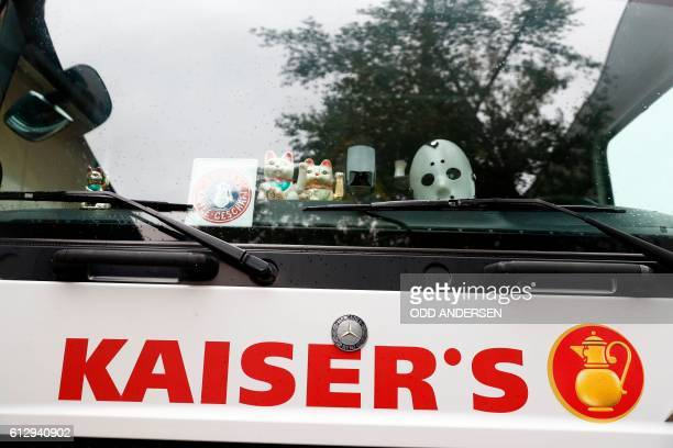 Chinese fortune cats and a mask are seen behind the windscreen of a truck with the logo of German retail chain Kaiser's of the Kaiser's Tengelmann...
