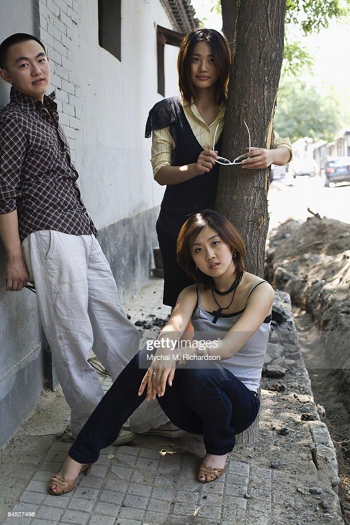 Chinese friends standing on sidewalk : Stock Photo