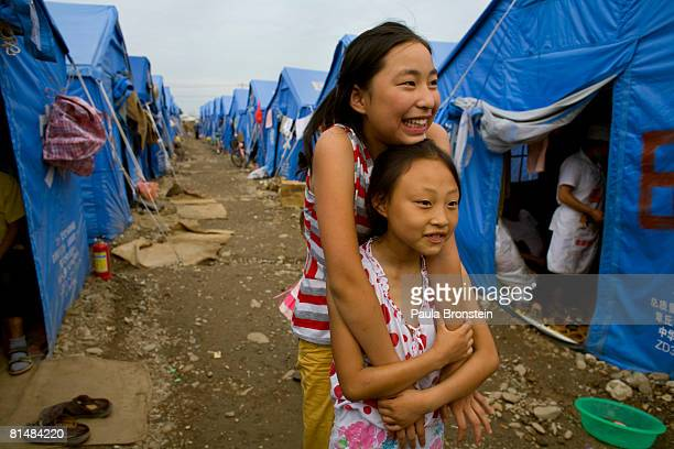Chinese friends walk near their tent in a muddy refugee camp after rains soaked the area where thousands live in Mianzhu Sichuan province China...