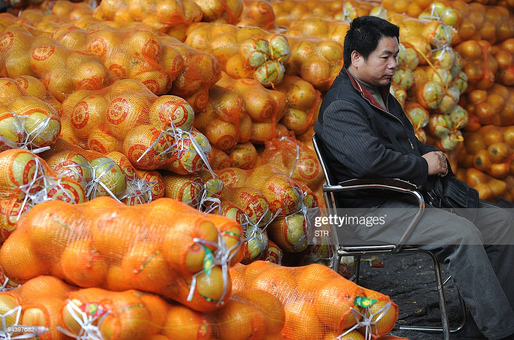 A Chinese fruit seller sits with his stock of fruit ahead of the upcoming festive seasons in Hefei in eastern China's Anhui province on December 13...