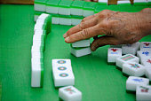 An elderly hand making a move in a Chinese game.