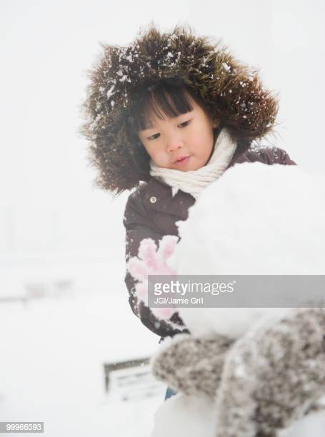 Chinese girl building snowman