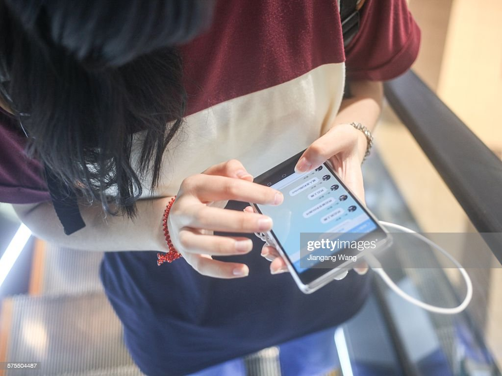A Chinese girl chatting with WeChat on smartphone on a moving escalator in Japan