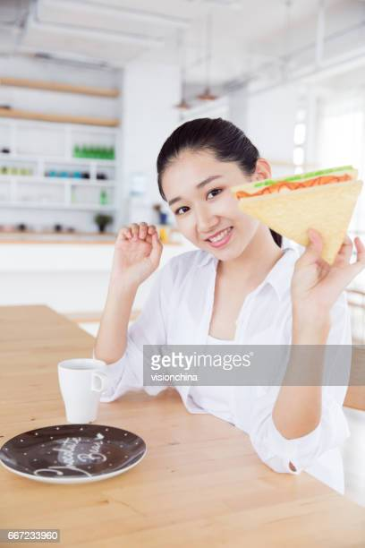 chinese girl eating breakfast in the kitchen