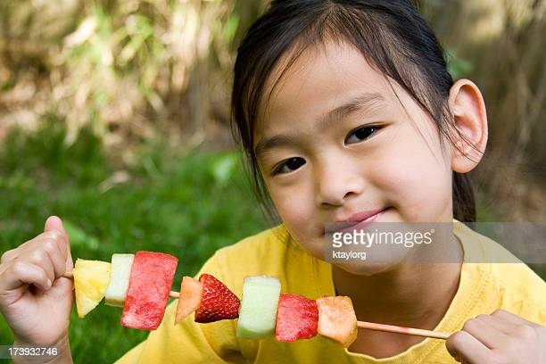 Chinese girl holding fruit snack