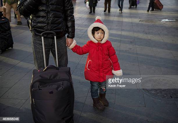 Chinese girl holds her fathers hand as they wait to board a train for the Spring Festival at a local railway station on February 17 2015 in Beijing...