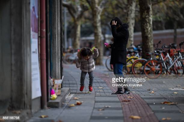 A Chinese girl jumps while on a sidewalk in Shanghai on December 8 2017 / AFP PHOTO / CHANDAN KHANNA