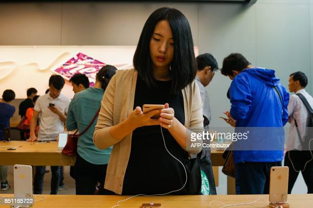 A Chinese girl looks at the Apple iPhone 8 Plus displayed in an Apple showroom in Shanghai on September 22 2017 Apple iPhone 8 and 8 Plus went for...