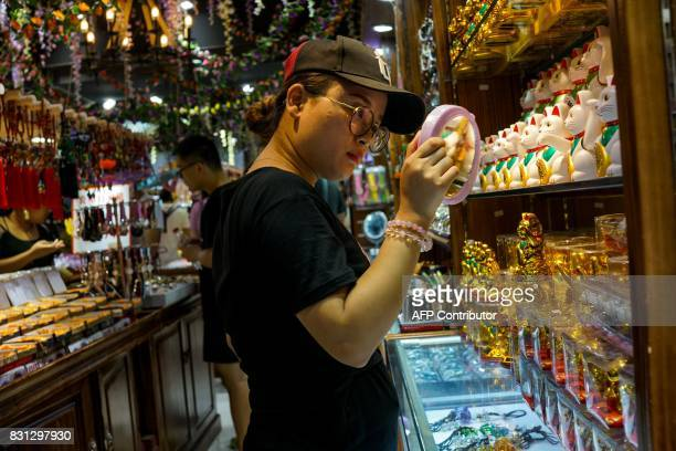 A Chinese girl looks in a mirror as she shops inside a store in Shanghai on August 14 2017 China's industrial output a key engine of growth slowed...
