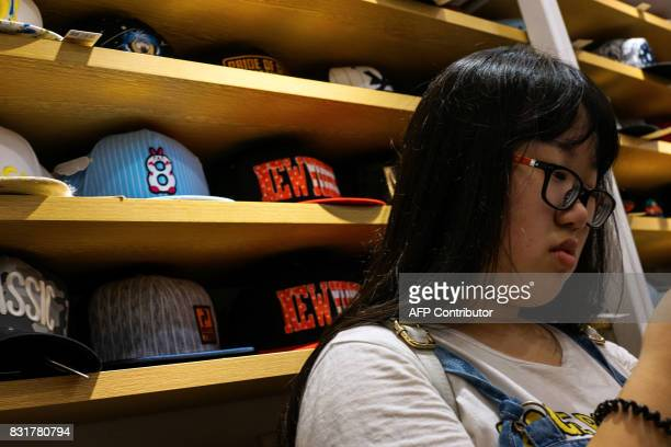 A Chinese girl looks on as she buys a cap inside a shop in Shanghai on August 15 2017 Trade tensions between the United States and China heated up on...