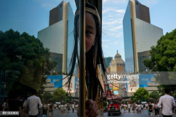 A Chinese girl looks out from a tram in Shanghai on August 14 2017 / AFP PHOTO / CHANDAN KHANNA