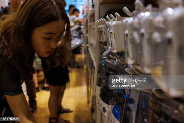 A Chinese girl looks through copies of Apple earphones inside a shop in Shanghai on August 15 2017 Trade tensions between the United States and China...