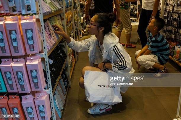 A Chinese girl looks through products as she shops inside a store in Shanghai on August 14 2017 China's industrial output a key engine of growth...