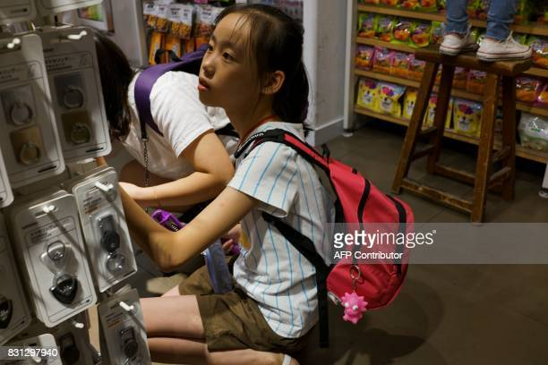 A Chinese girl looks through the products as she shops inside a store in Shanghai on August 14 2017 China's industrial output a key engine of growth...