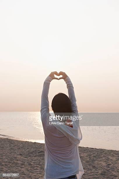 Chinese girl making heart shape on beach