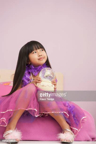 Chinese girl playing with snow globe