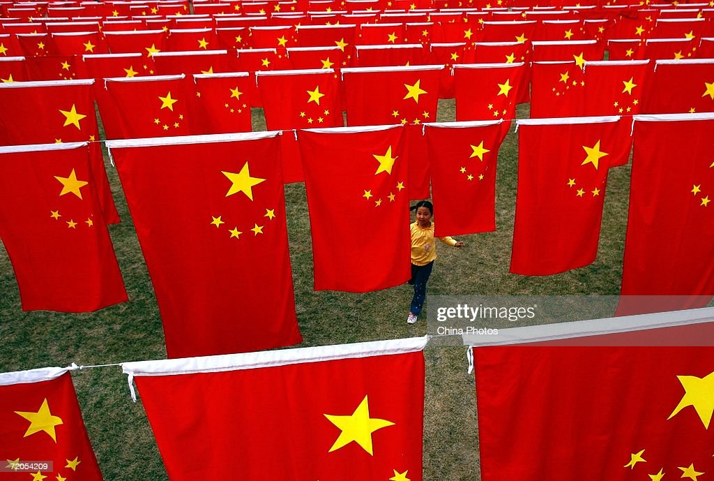 A Chinese girl runs between China's national flag at Chaoyang park September 30, 2006 in Beijing, China. Chinese people are preparing for National Day Celebration, the 57th anniversary of the founding of People's Republic of China which falls on October 1.