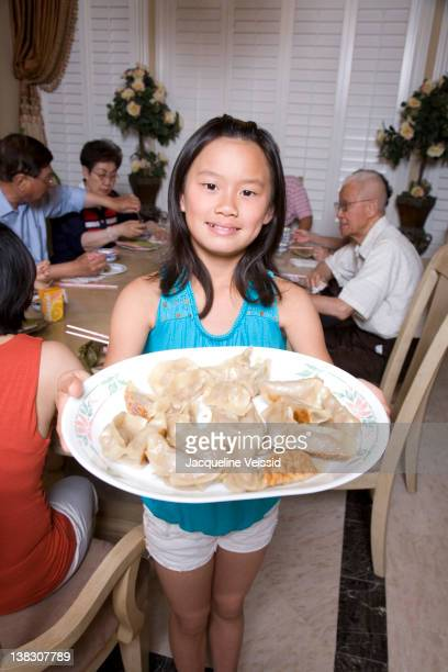 Chinese girl serving family dumplings