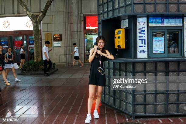 A Chinese girl talks on a pay phone in Shanghai on August 14 2017 China's industrial output a key engine of growth slowed sharply in July as...