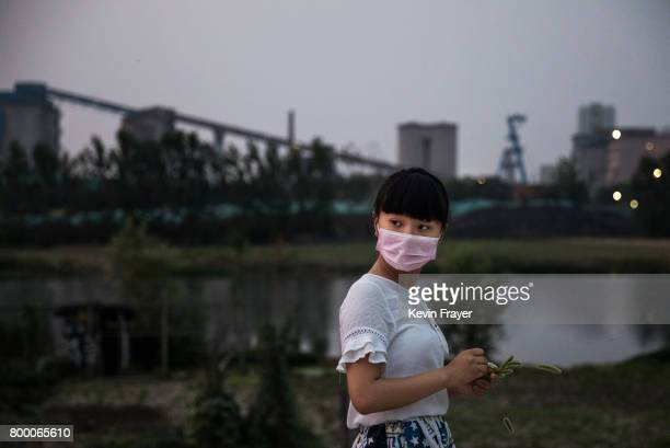 Chinese girl wears a mask as she walks near the main shaft of the Panji No 1 coal mine close to the site of a large floating solar farm project under...