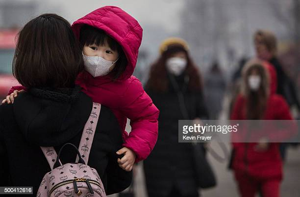 Chinese girl wears a mask to protect against pollution as she is carried in a shopping district in heavy smog on December 8 2015 in Beijing China The...