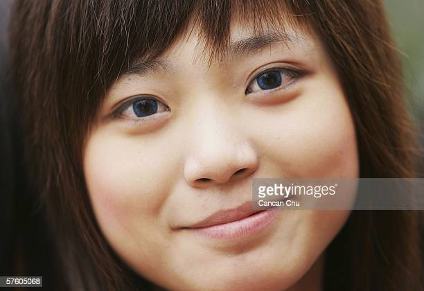 Chinese girl wears blue contact lenses before she attends a selective process of the 'Super Girl Voice' TV on May 13 2006 in Chengdu of Sichuan...