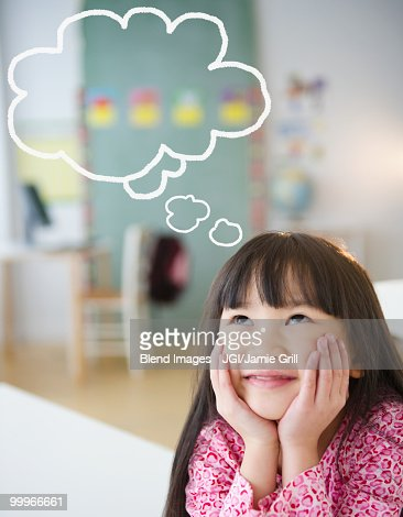 Chinese girl with thought bubble in classroom : Stock Photo
