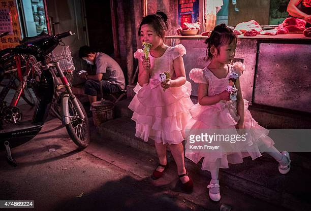 Chinese girls dressed for a party eat ice cream as they stand in front of a butcher shop in a residential street on May 27 2015 in Beijing China