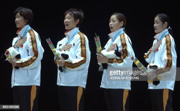 Chinese gold medalist women fencers sing their national anthem during the awards ceremony for the women fencing sabre team event at the14th Asian...